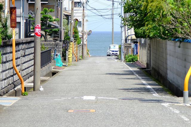 画像: 船守神社から黒崎の浜を目指して住宅街を歩きます。道の向こうに海が見えてきて、素敵な景色です。