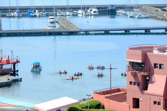 画像: お天気最高の中、シーカヤックを漕ぐ学生たち。港はほとんど波がなく安全で、思いっきり楽しめる課外授業ですね。