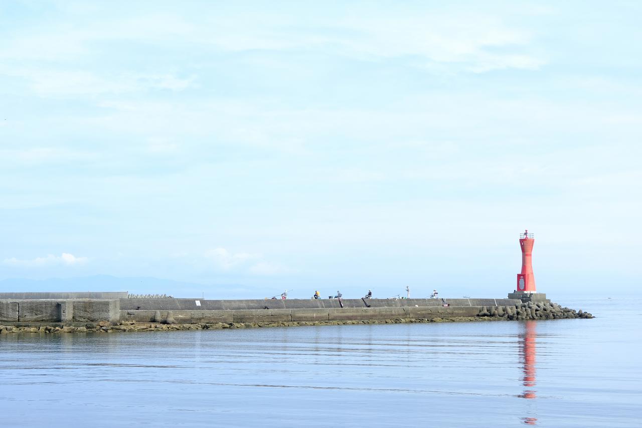 画像: 遠くにうっすらと見えるのは淡路島。赤い灯台が青い海に良く映えます。
