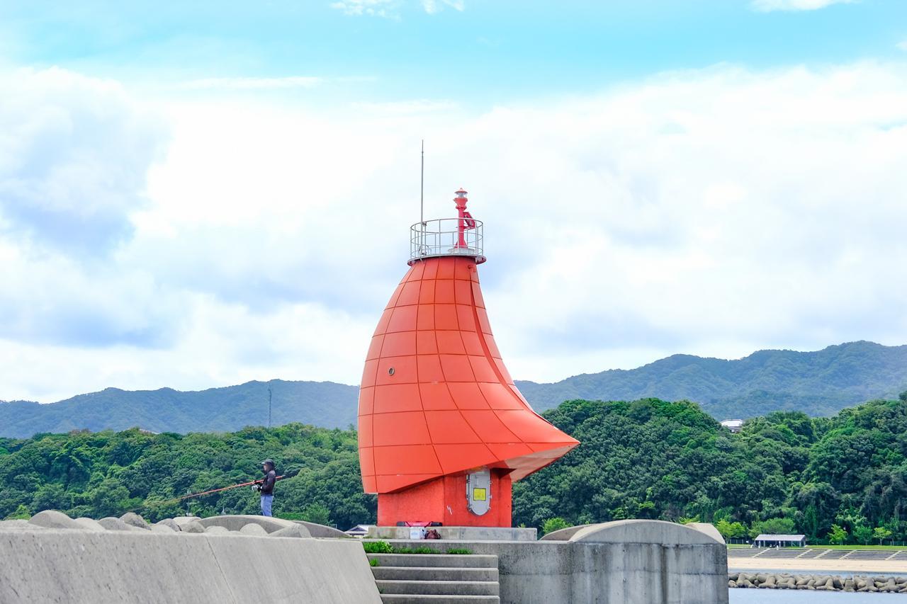 画像: 西防波堤灯台に到着しました。風に帆をなびかせる赤いヨットです。