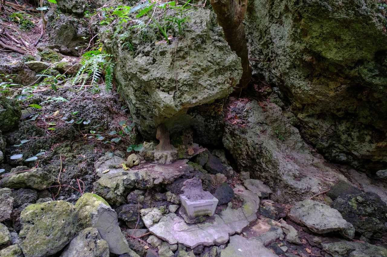 画像: ヤハラヅカサに降り立ったアマミキヨが仮住まいした場所「浜川御嶽」。エメラルドブルーのビーチすぐ横に位置していて、生活と神とが近い場所に存在していることがわかります。