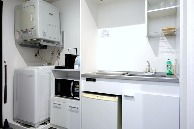 画像: 部屋入口には冷蔵庫、洗濯機などの家電、コンロがあるキッチン。お皿やグラスも揃っています。