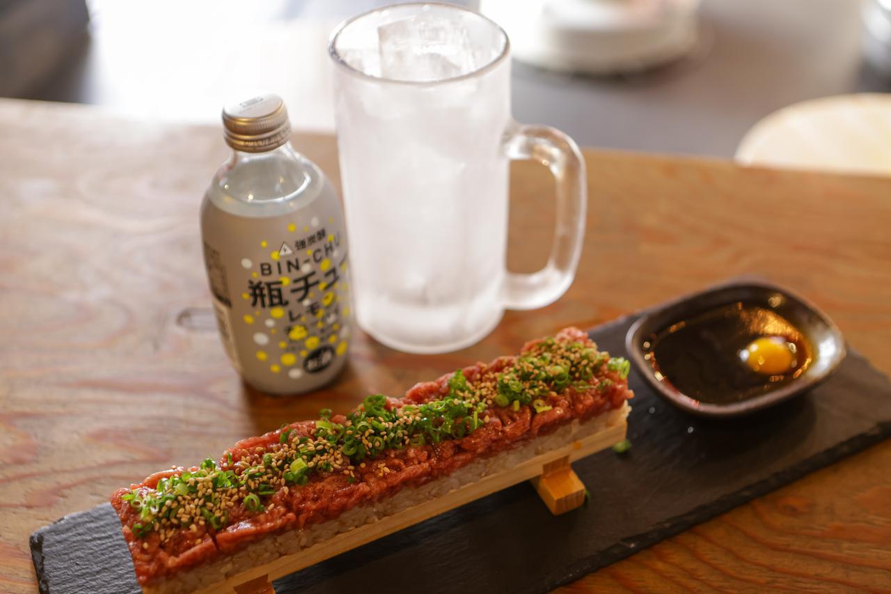 画像: 玄米を混ぜたご飯の上にユッケをのせたユッケ寿司と津山で人気の瓶入りチューハイ「瓶チュー」