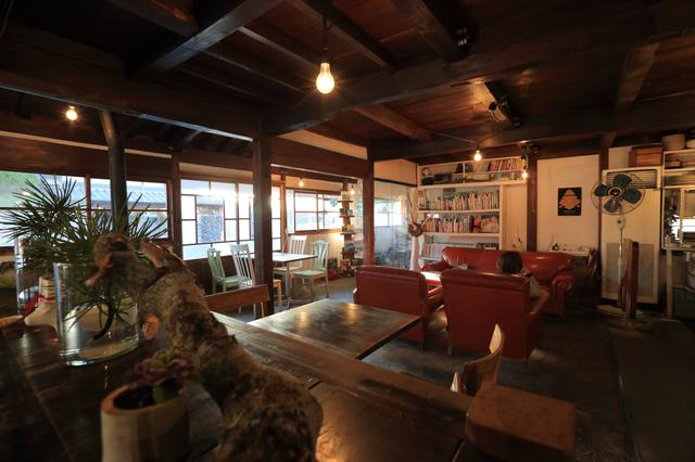 画像: 赤いソファーは、米軍基地で利用されたもの。いろいろなイスとテーブルが並んでいる店内は、とっても個性的