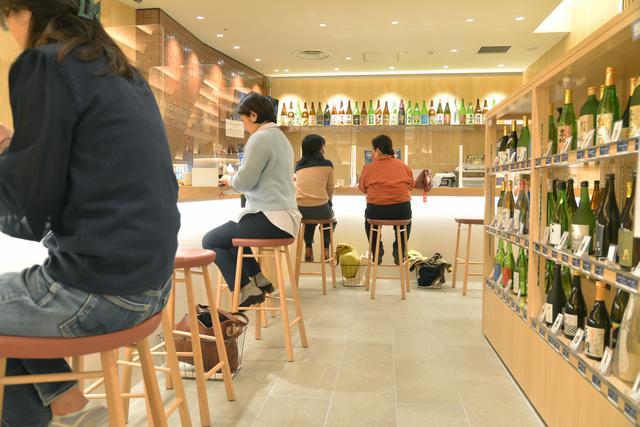 画像: 店舗奥のカウンターエリア「ご縁カフェ」。しじみ汁と漬け物付きの「のどぐろ丼セット」は1,200円(税込)。3種選んで楽しめる「地酒呑み比べセット」(1,000円・税込)も人気