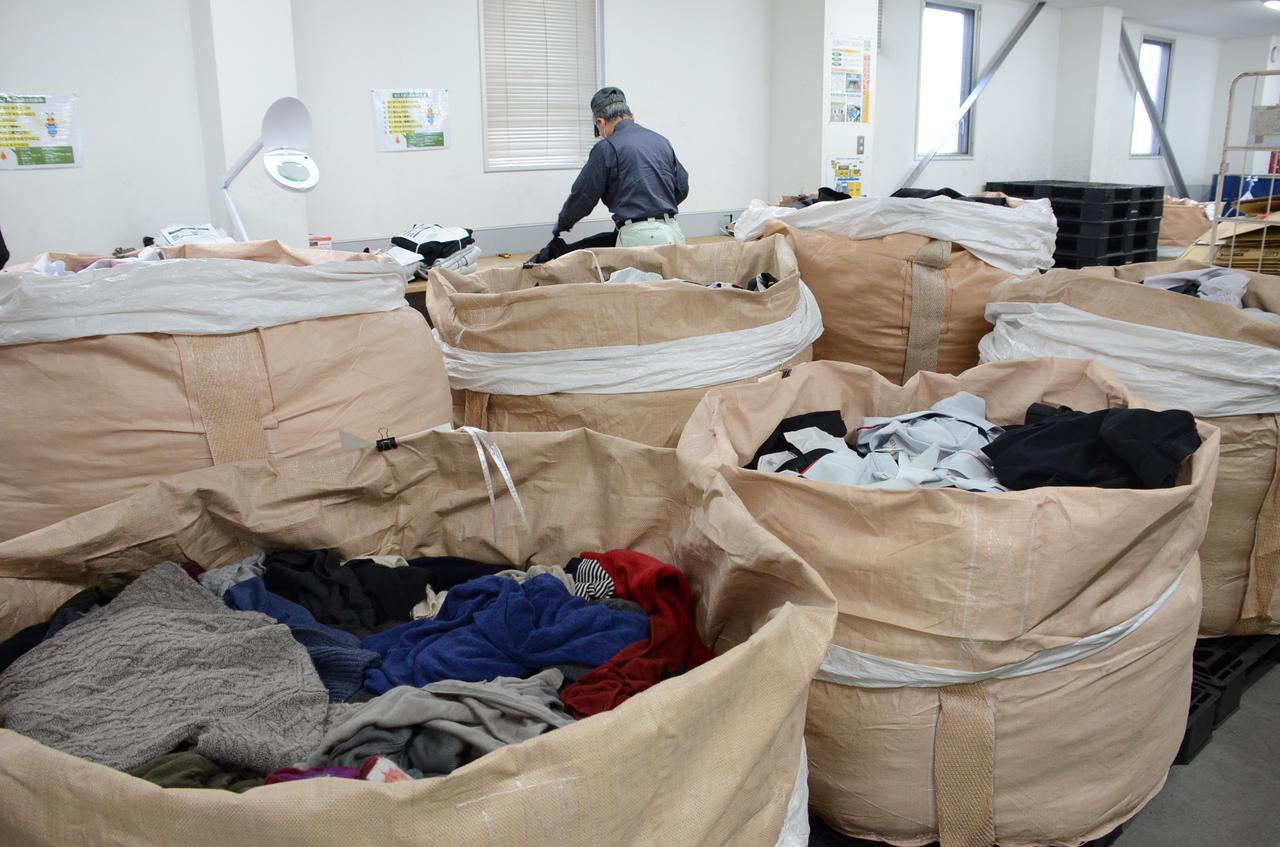 """画像1: 原料は""""綿""""。25万着を回収し、仕分け作業"""