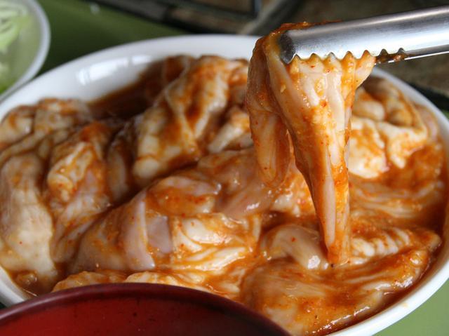 画像: ホルモンはさまざまな部位が入っている。味噌ニンニクだれに浸かる