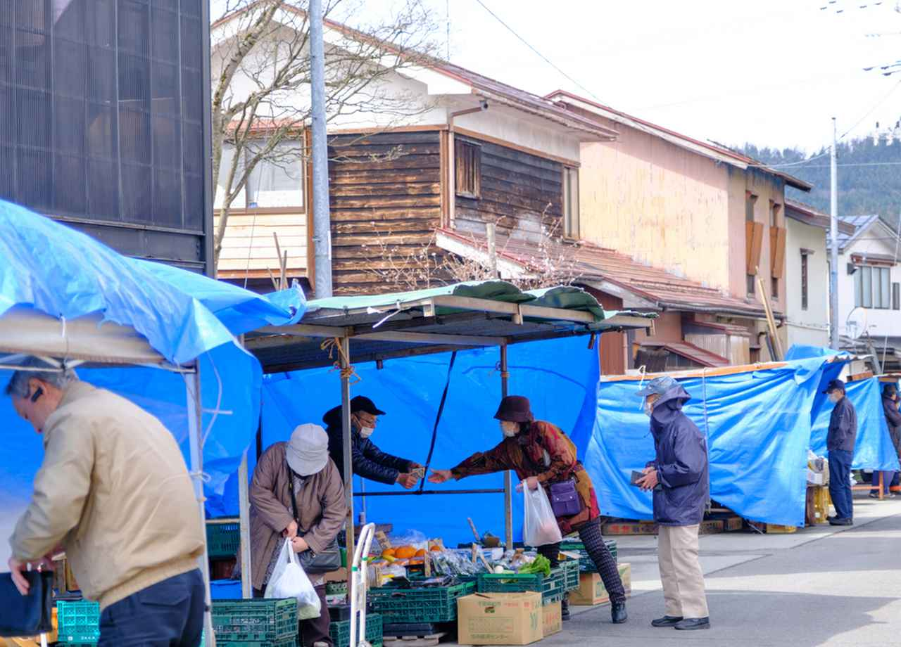 画像: 30店ほどが立ち並ぶ朝市。人気の鮮魚店やお惣菜屋、八百屋など日常の品々を買う人々が訪れます。
