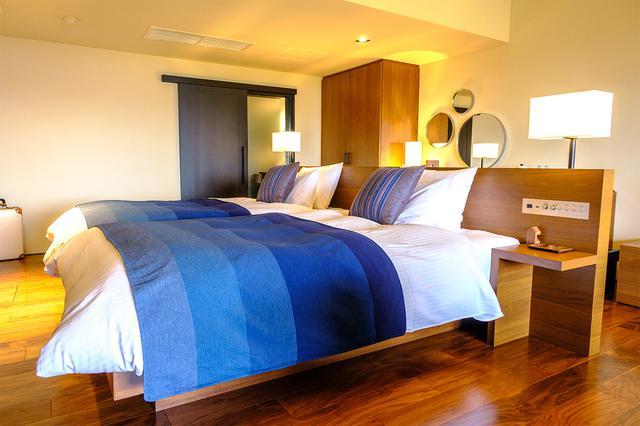 画像: 藍染のベッドカバーがかけられたベッド。無駄のない部屋で清掃も行き届いています。