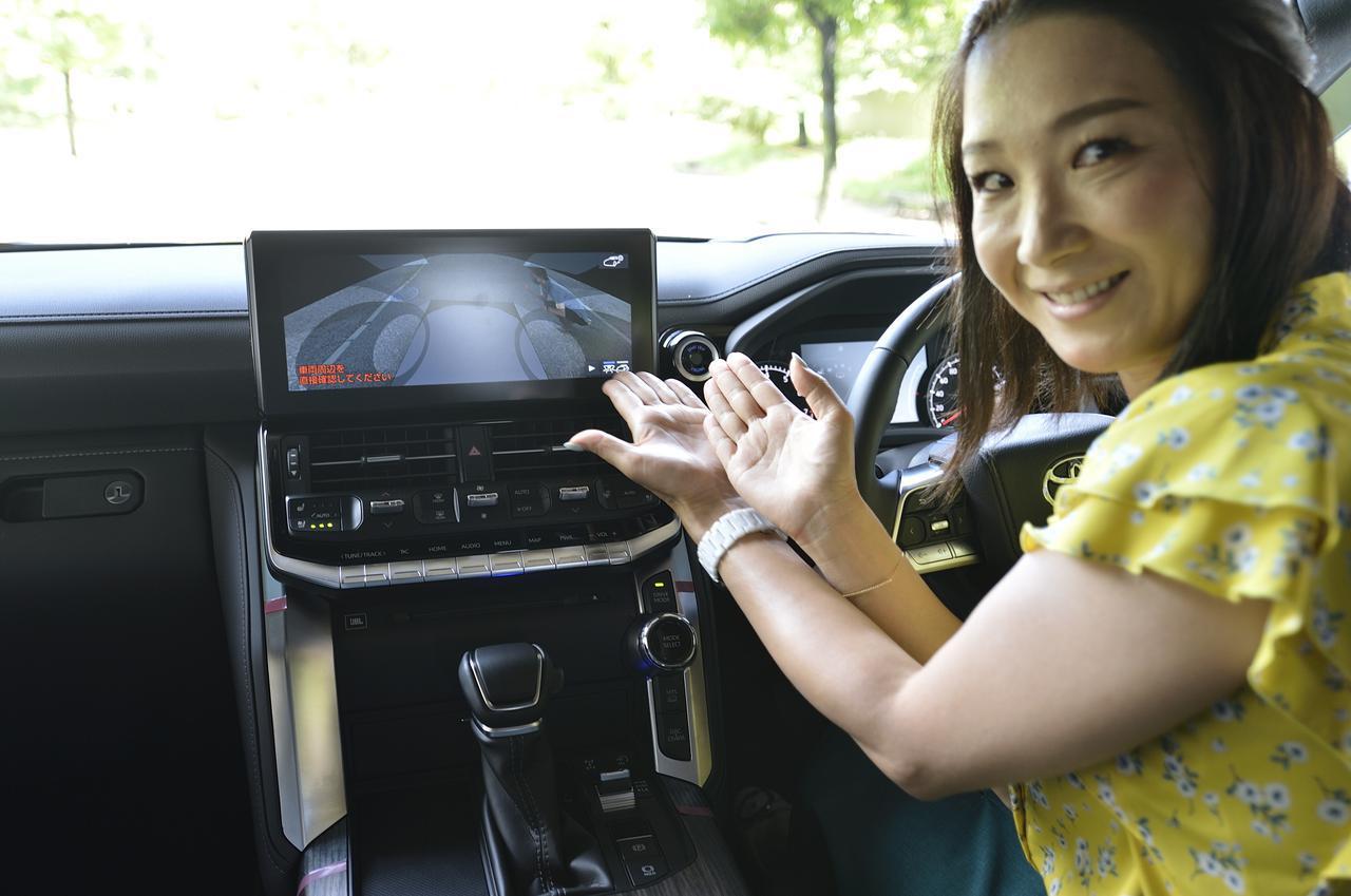 画像: トヨタ初のアンドーフロアビュー。フロントに内蔵されたカメラが車両周辺の画像を合成。車両下の状態や後輪の位置を確認できるすごい機能なんです。試しにタイヤそばにしゃがみこんで見るスタッフ。写真でご覧いただけますでしょうか?