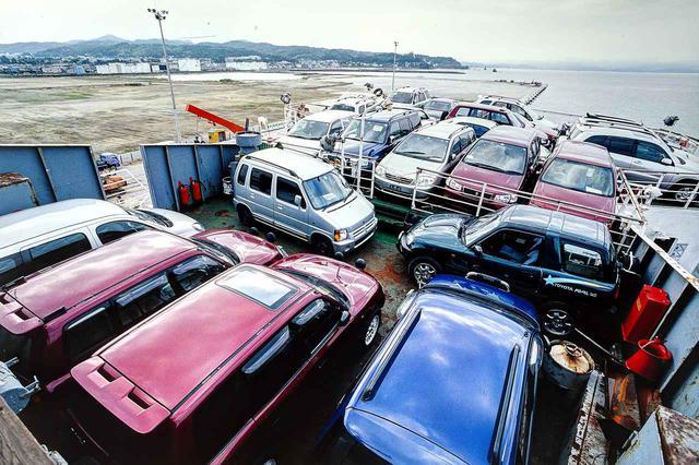 画像: 日本を出港する前の「RUS」号。甲板にも車両を満載するために、クレーンを使用していたのだ。大量の中古車。