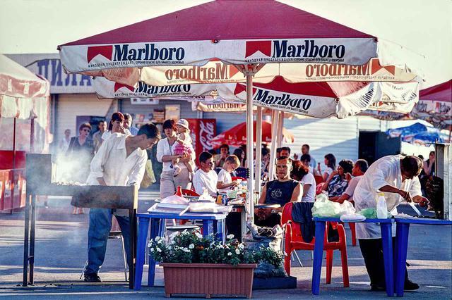 画像: 2003.8.3/ウラジオストク。海沿いにヨットハーバーがあり、その脇に大きな公園があった。バーベキューなどでくつろぐ人々。見慣れたカラーリングとロゴのパラソルが、ここがロシアであることをしばし忘れさせた。