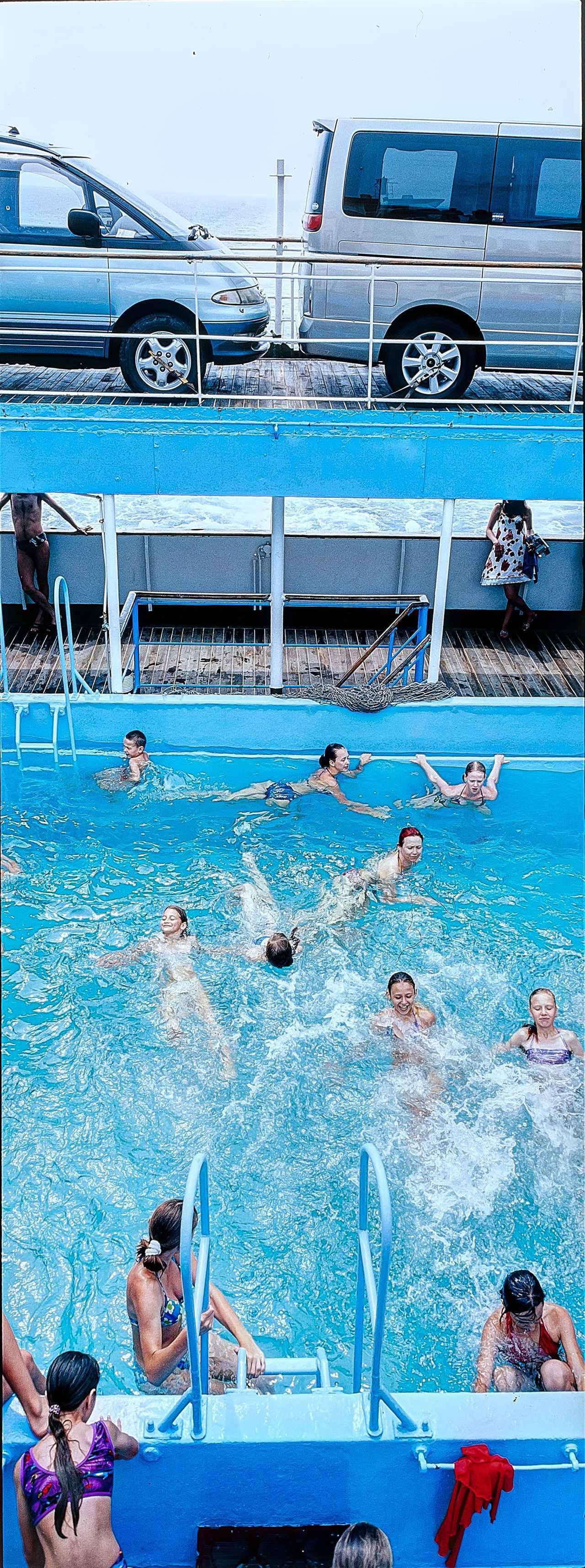 画像: 富山の伏木港からウラジオストクに向かう大型フェリー「RUS」号には、立派なプールが備え付けられていた。デッキ上のクルマを見上げながら、水とたわむれて盛夏を満喫する子供たち。
