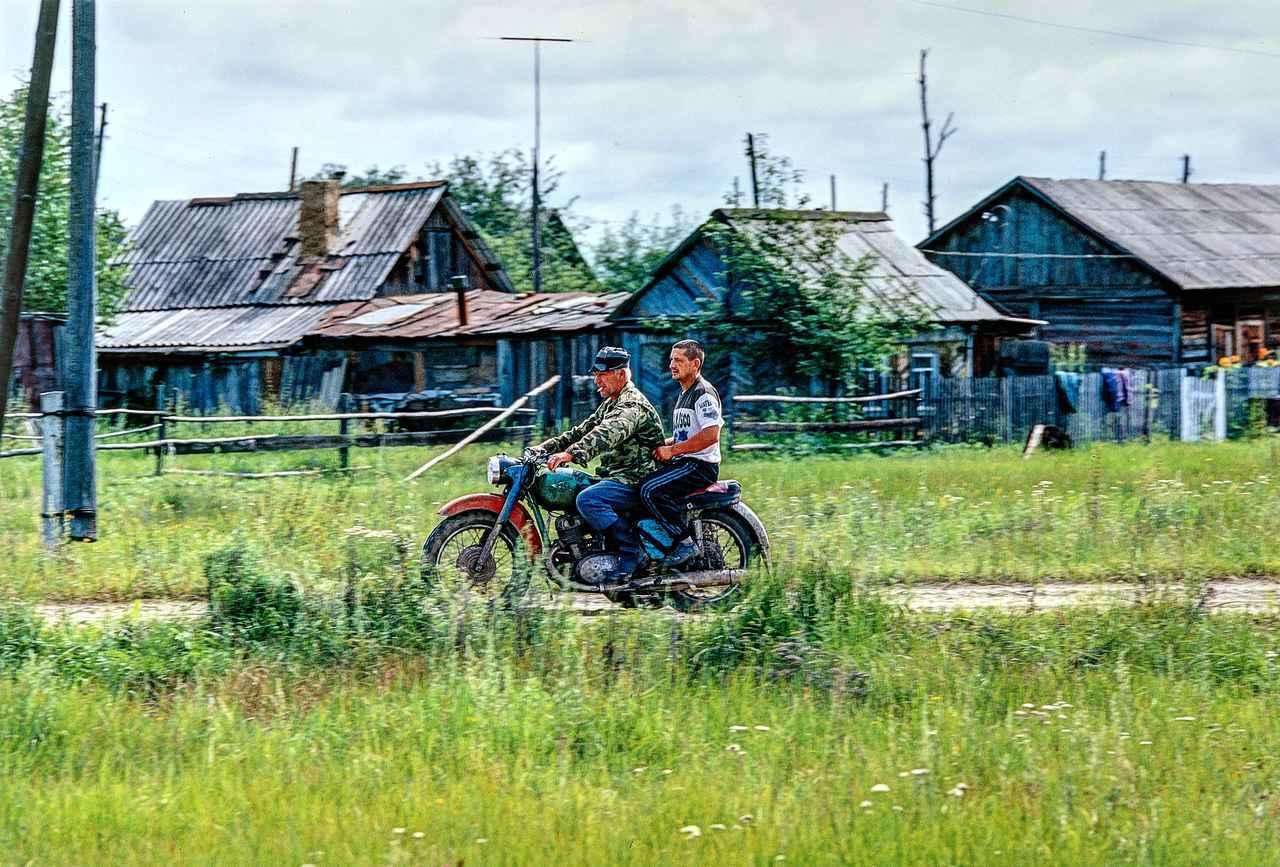 画像: 古くさくも豪快な排気音とともに走っていった大型バイク「ウラル」。BMWに範を取ったモデルだ。そして質素な造りの家々。