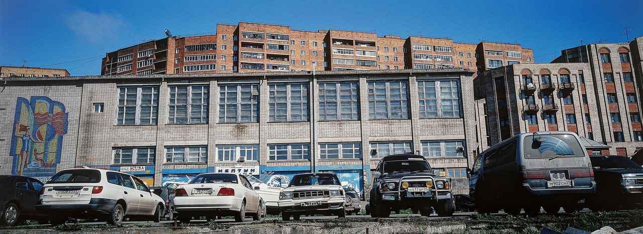 画像: 駐車されているクルマを見ると、ここがロシアのウラジオストク市内と思えないほどに日本車だらけ。旧来工法の堅牢そうな構造の建物が、日本とは異なる雰囲気を醸し出す。