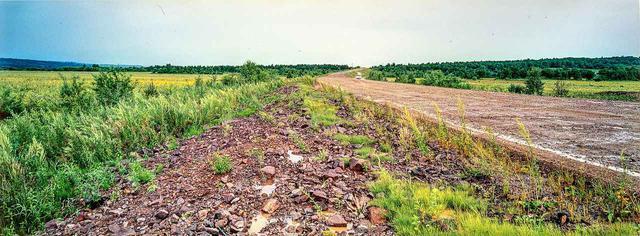 画像: 03年8月7日。ウラジオストクからハバロフスクをすぎ、さらに西へ進むと現れた未舗装の路面。はるか向こうに、水しぶきをあげながら走る1台のクルマが見える。