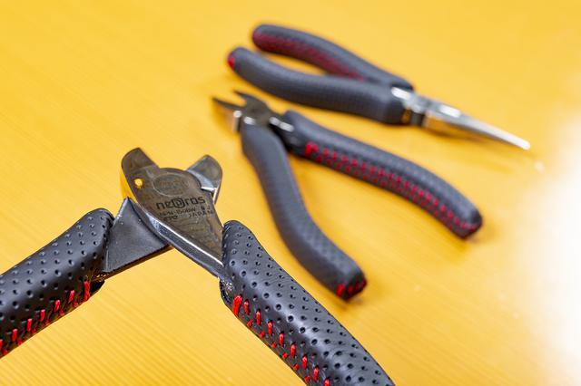 画像: 牛革と巻き付け縫製、そして縫い方の千鳥縫いは、クルマの革巻きハンドルと同様である。赤と黒のコントラストが高級さを表現している。