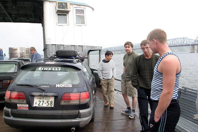 画像: ニジニ・ノブゴロド市を目指しているときに乗ったフェリーの船上にて(連載Vol.13参照)。日本ナンバーのカルディナを珍しそうに見る右側の2人は、船に乗り合わせた他者のドライバーたち。その隣が、ロシア後半での通訳を担当してくれたアレクセイさん。