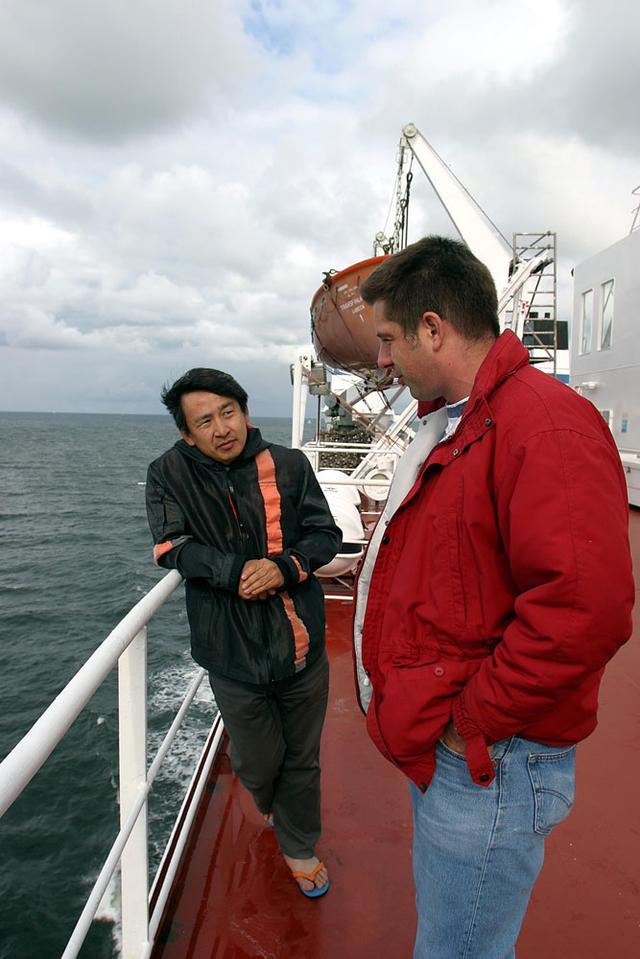 画像: 海面を吹き抜けていく風を受けながら、トランスフィンランディア号のデッキで、暇をつぶす金子氏。ビーチサンダル仕様。