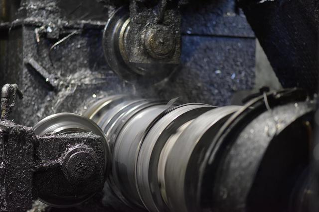 画像: 写真中央はセットされたホイール。ここに回転した金属板を押し当て引き伸していく