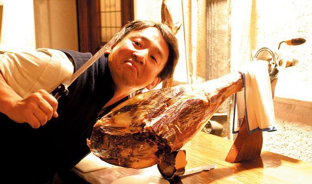 画像: 白豚の後ろ脚のみから作られるスペイン産の生ハム「ハモン・セラーノ」。骨と蹄が付いた美味なる塊を前に、「食うぞ」とおどけてみせる。