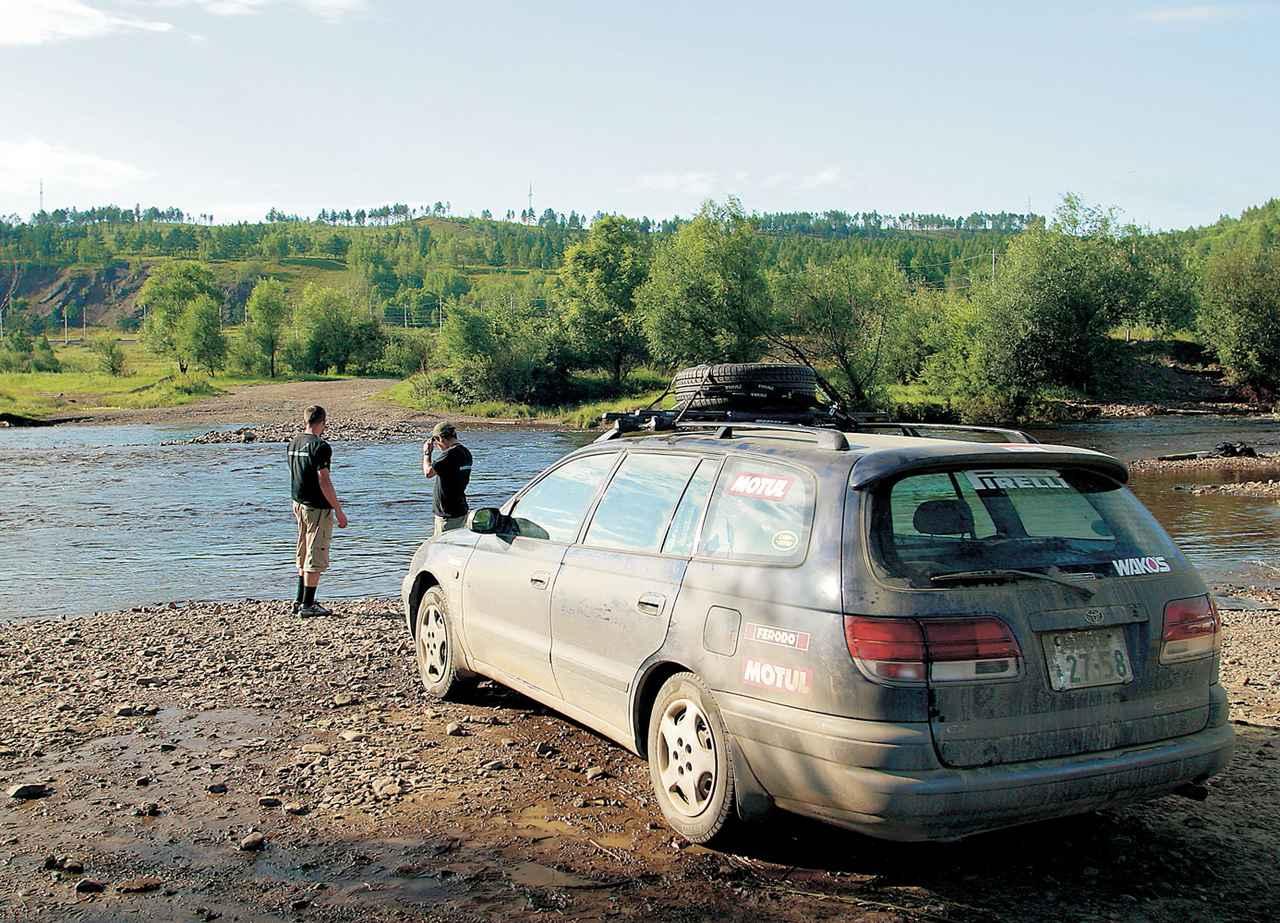 画像: 2003年8月、ユーラシア大陸横断中のシーン。場所はロシア東部のスコボロディノ。この付近は道路の状態があまりにも悪く、ここから約1000km西方にあるチタまでは列車に載せて移動させることにした。悪路走行で汚れたカルディナを洗うためにやってきた川辺。夏だが水は驚くほど冷たかった。