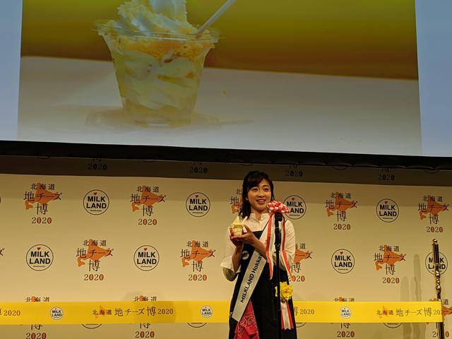 画像: 北海道地チーズソフトクリームを試食する黛英里佳さん