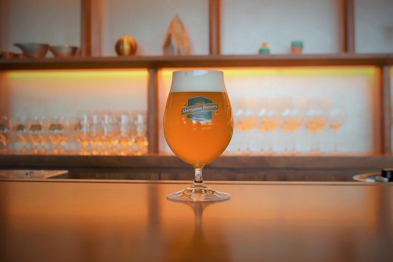 """画像: 限定醸造のシャルドネエール。「SHIROYAMA HOTEL kagoshima(城山ホテル鹿児島)」は2021年2月5日発行の『ワイン王国』にてご紹介したラグジュアリーホテルだ。ワイン王国編集部が取材をした正にその日に、ホテル内のビール醸造所では""""ワインのようなビール""""の仕込みが行われていた。2か月の発酵と熟成期間を経て2月の某日、ホテル内のバーでお披露目された"""