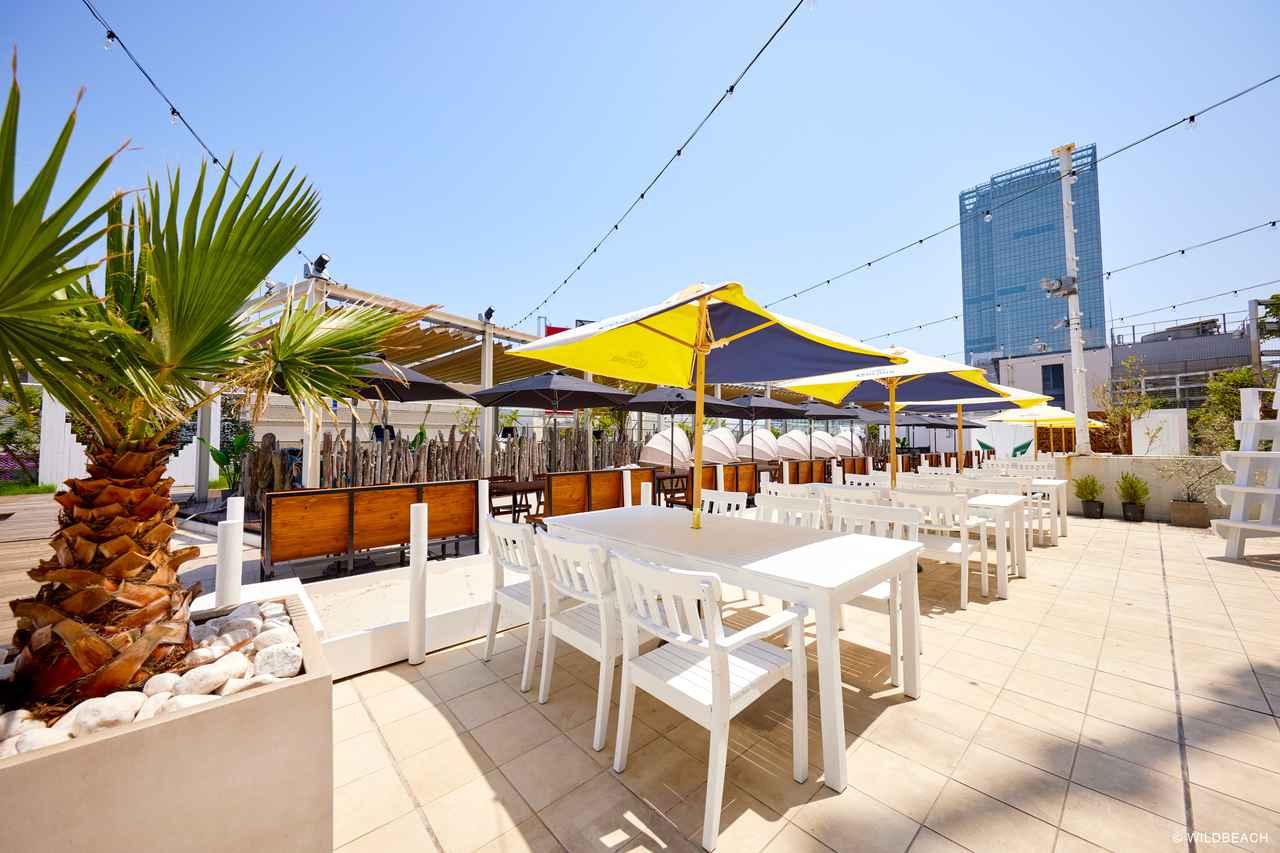 画像: 抜けのよい「ランウェイビーチ」はビーチリゾート風な世界観。テーブル席は40メートルのランウェイビーチを囲んでいる。夕方〜夜にはライトの演出も