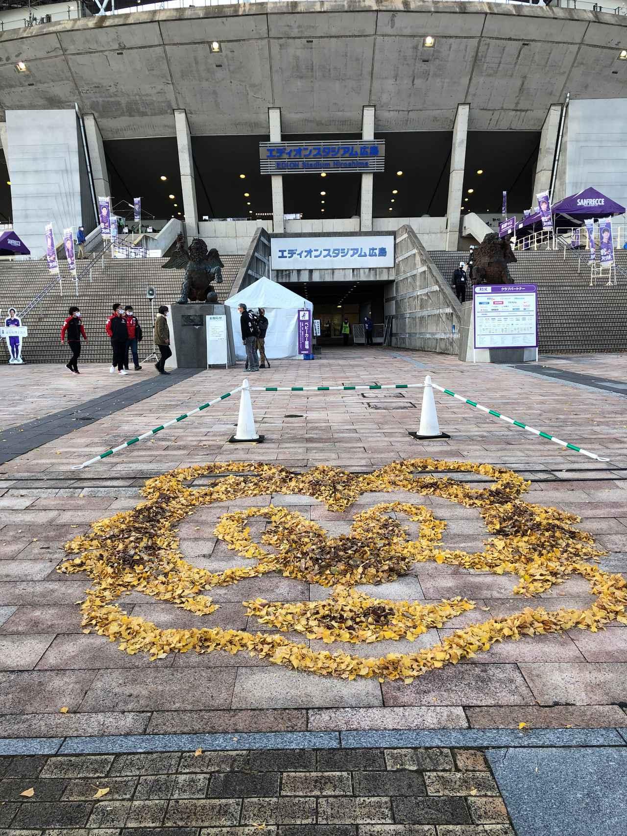 Images : 2番目の画像 - エディオンスタジアム広島の周辺では、いちょうの鮮やかな黄色が。落ち葉を片付けていたスタッフが、サンチェの顔を作って来場者をもてなした(写真◎石倉利英) - サッカーマガジンWEB