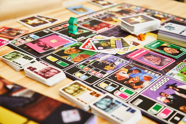 画像: ボードのマス目には、「A」「E」などの手持ちの人物カードを示すアルファベットが書かれている。アルファベットは商談を成立させる条件を示している。