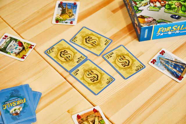 画像: 後半に行う売却パート。この写真の場合、「29」と記された高層ビルのカード(右)を出した人が、もっとも高額な「$14,000」カードを手に入れることができる。