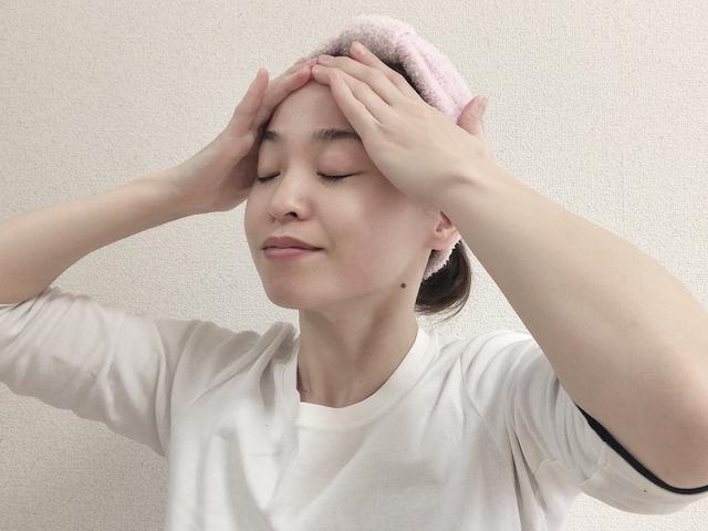 画像: 顔の筋肉を持ち上げるイメージで、ゆっくりとおでこを通って生え際まで手を滑らせます。この動きを10回ほど繰り返します。