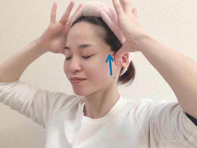 画像: 耳の付け根(耳たぶの横)の部分を親指で軽く押します。押しながら、下から上に向かってゆっくり親指を滑らせます。この動きを、10回ほど繰り返します。