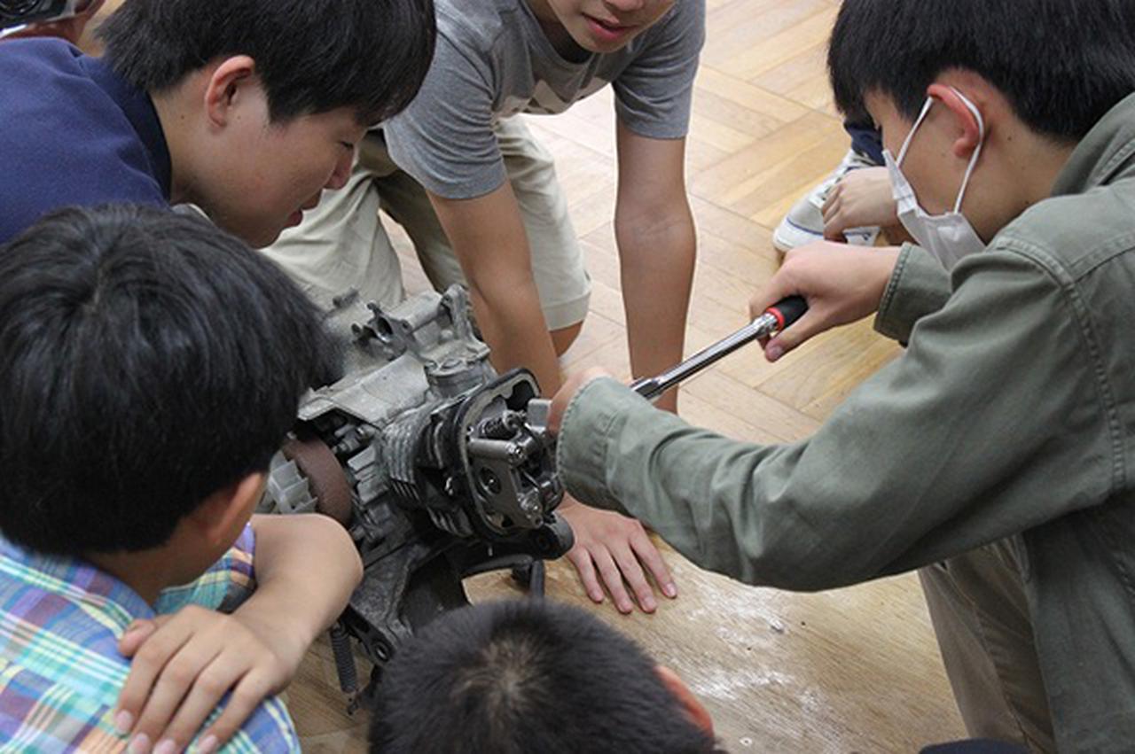 画像: 生徒たちは二輪車販売店からのアドバイスを受け、興味津々の表情で自ら工具でバイクの組み立てを行う