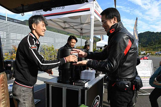 画像: スタッフから笑顔でコーヒーを受け取る参加者