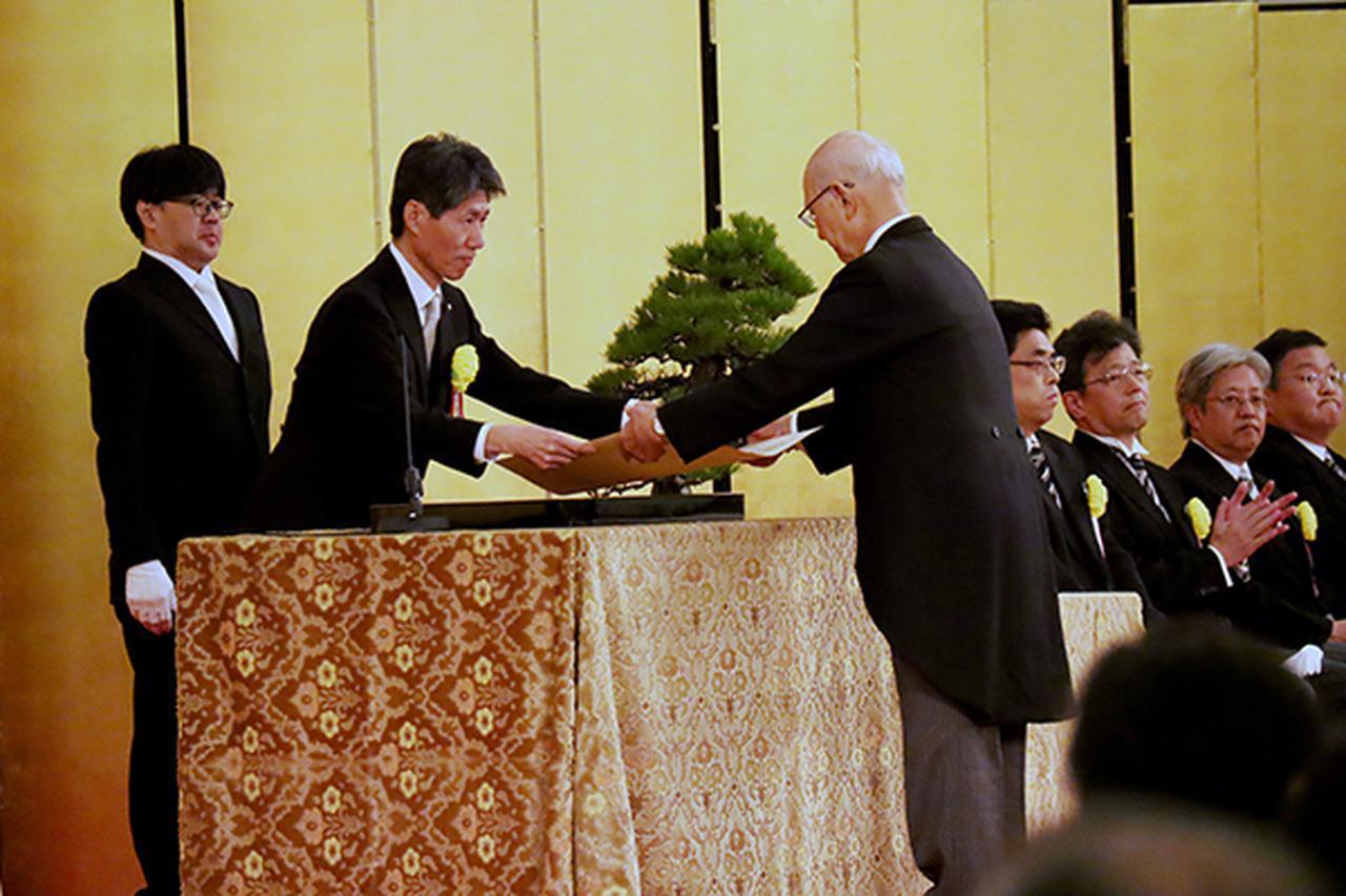 画像: 受賞者代表に勲章を伝達する磯﨑経済産業副大臣(左)