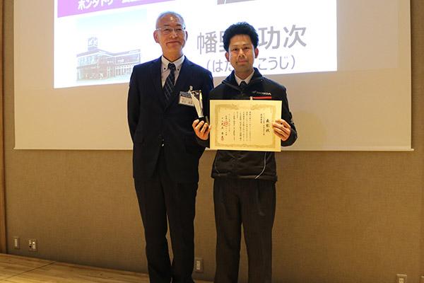 画像: サービス部門(HMSE3級)表彰。足立会長(左)と最優秀賞の幡野功次さん