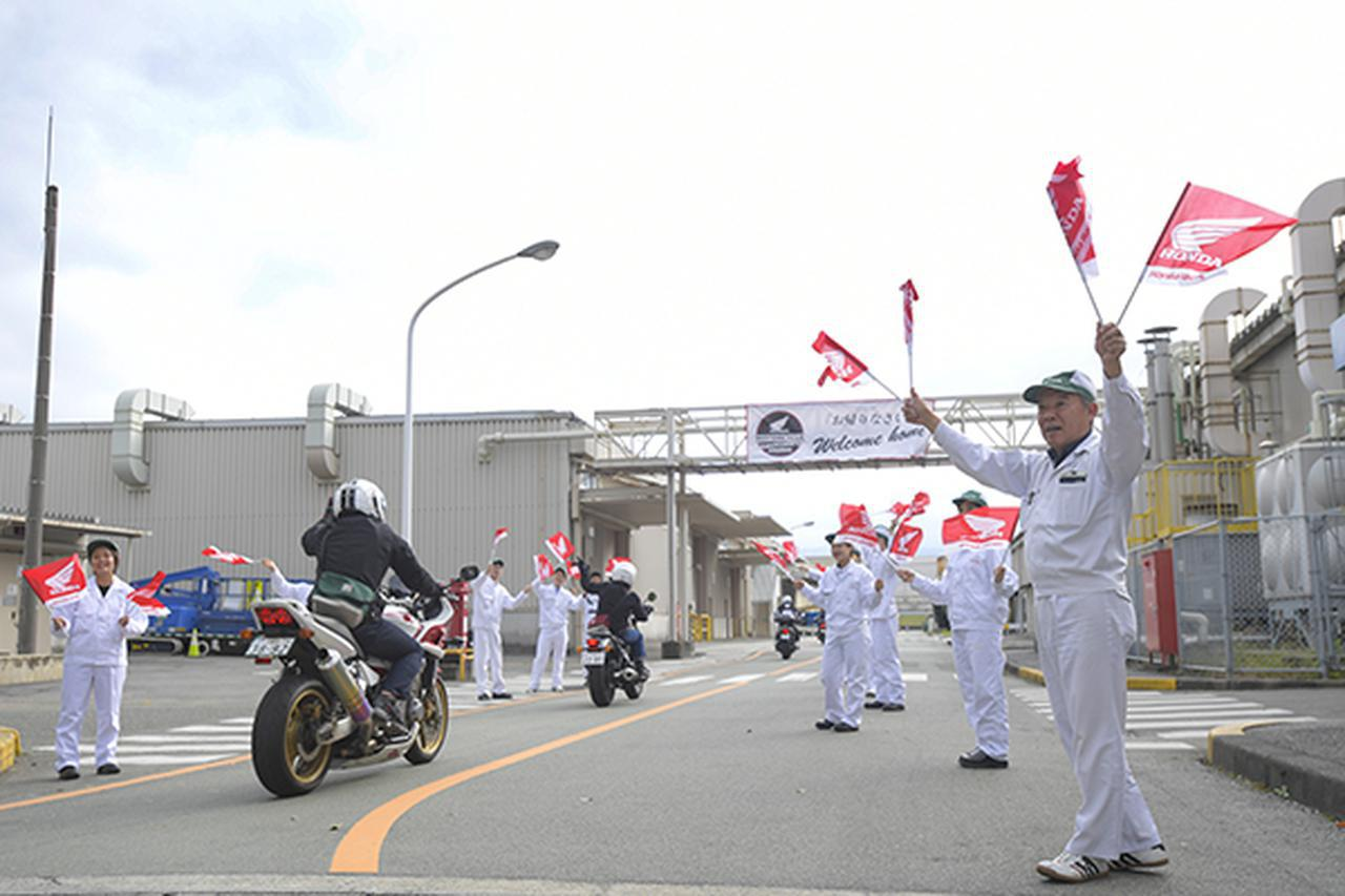 画像: 「お帰りなさい」と声をかけ旗をふる職員の間を来場者が進む