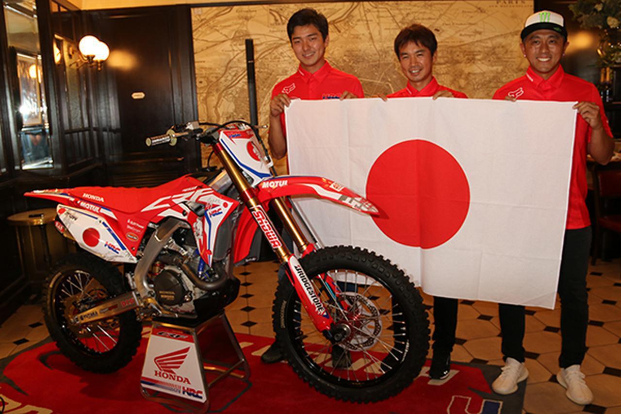 画像: 日の丸を手に笑顔を見せる右より成田亮選手、芹澤直樹監督、能塚智寛選手