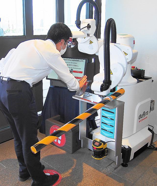 画像: 入館の際はカワサキ製ロボットが自動検温を行う
