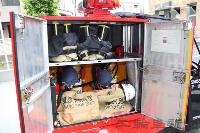 画像: 運転席側の収納庫には上下の防火衣が隊員分収納されている。上段にはズボン、下段にはジャケットとヘルメットが収められている。