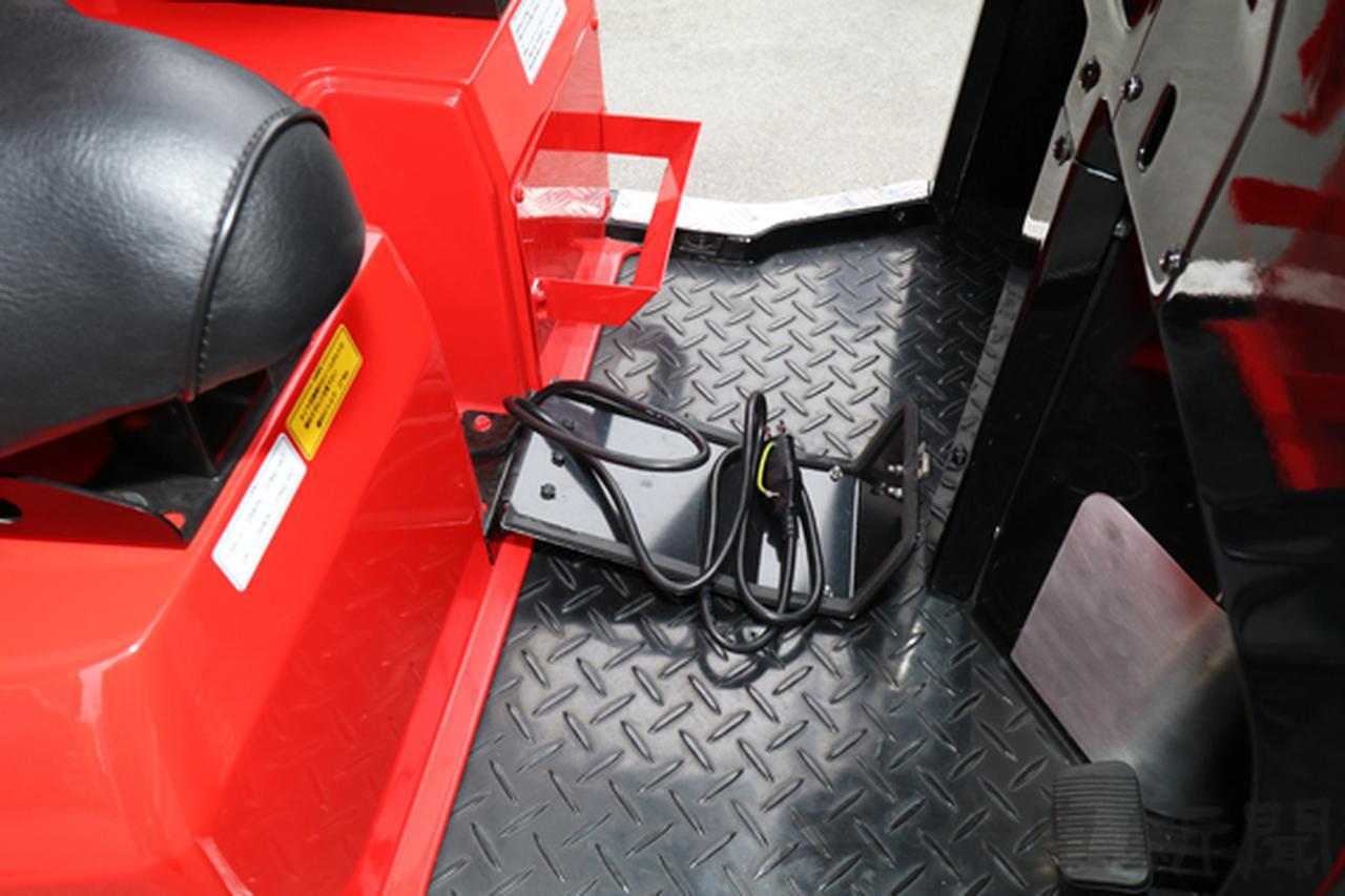 画像: 運転席と助手席の間に充電用ケーブルを内蔵する。