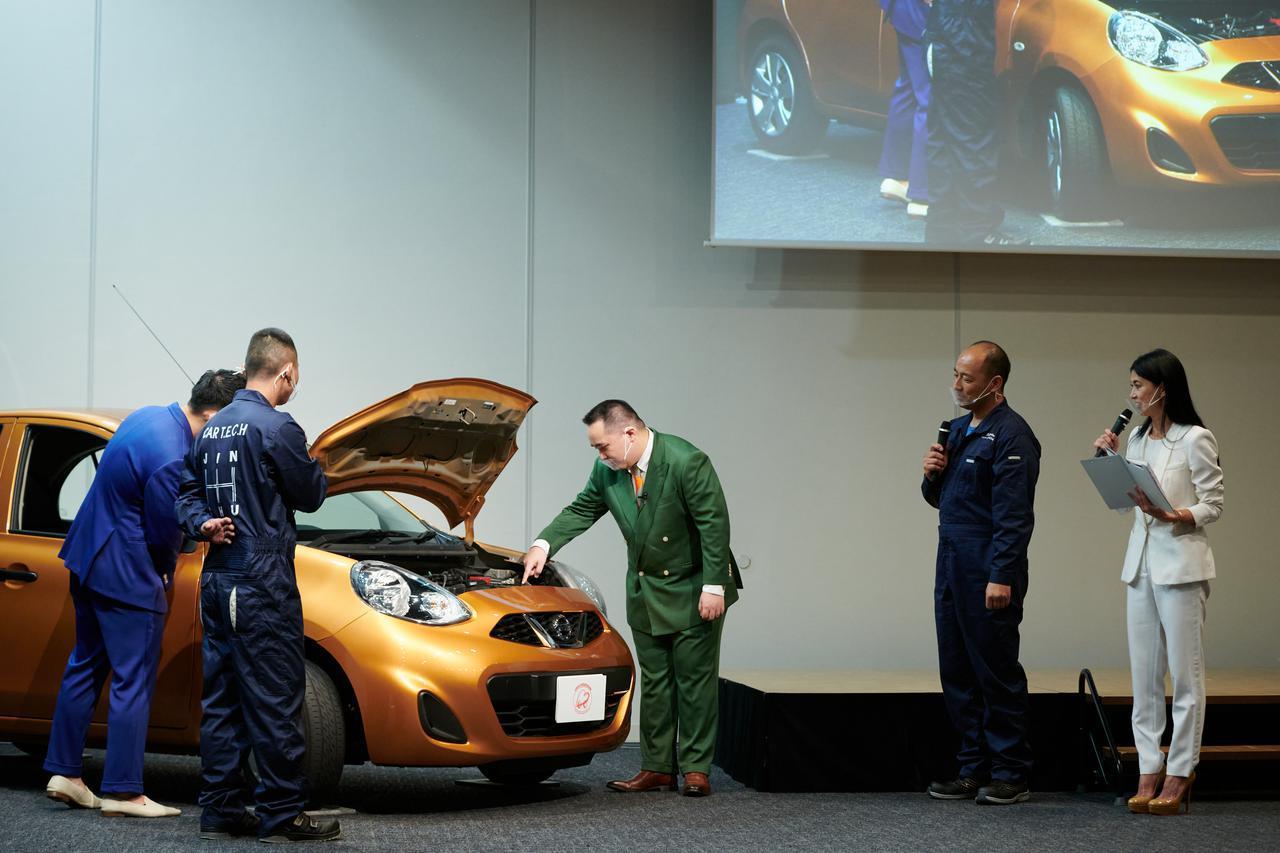 画像: 整備士日本一のアドバイスを受けながら日常点検デモンストレーションに臨むミルクボーイの2人