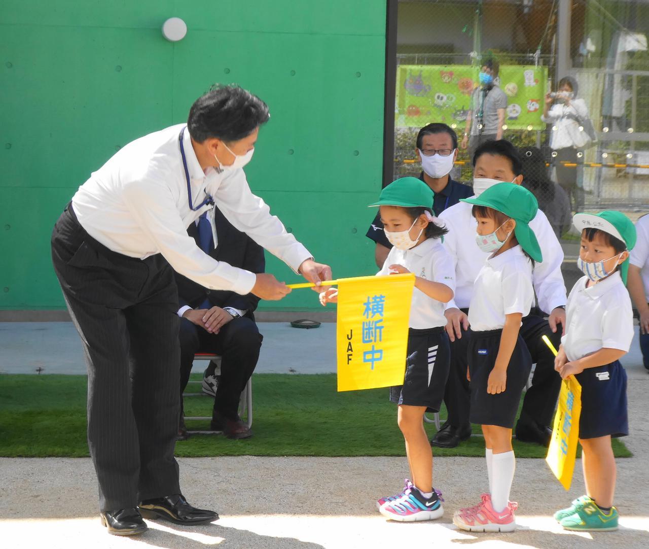 画像: キッズ・ゾーン設定式典で交通横断旗を受けとる園児たち