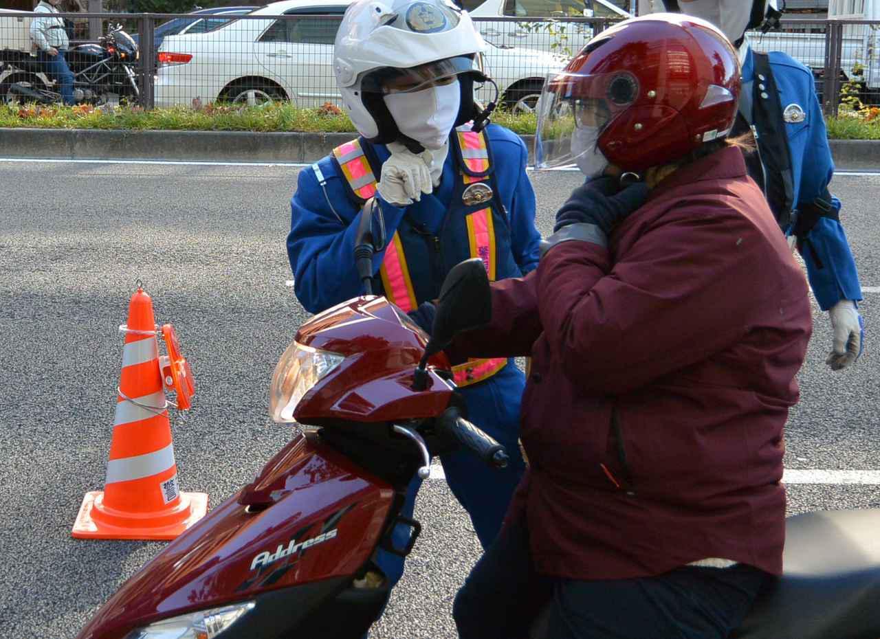 画像: ヘルメットのあごひもの正しい結着方法の指導
