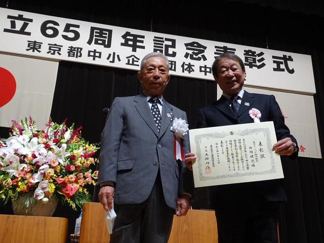 画像: 組合功労者132人を代表して東京都中央会の大村会長(左)から表彰状を授与されたAJ東京の野間理事長