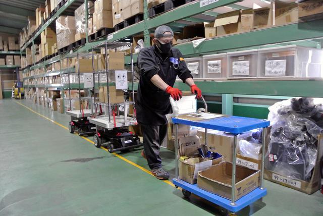 画像: 広い倉庫を搬送用ロボットが巡回し、人的移動時間を削減