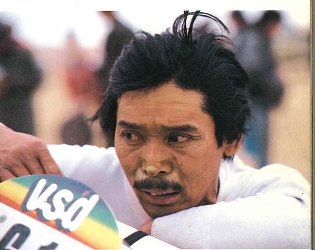 画像: 1985年、パリダカへ参戦時。1月8日、ニジェールにおいて撮影。「砂が顔のシワに沿ってたまり、ひどい顔になった」という浅賀さん(写真と文・出典:永岡書店昭和60年発行「JAPS WANT DESERT」より)