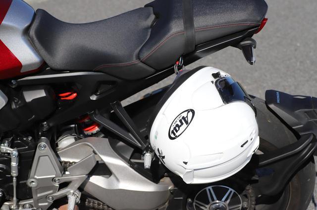 画像: タンデムシート裏にヘルメットホルダー用ワイヤでヘルメットホルダーを使用するが、別体で装着してほしい。シート裏にフック用ベルトはあるものの、荷かけフックはなく、積載能力は高くない。